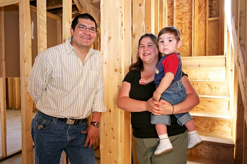 Family in front of partially constructed home
