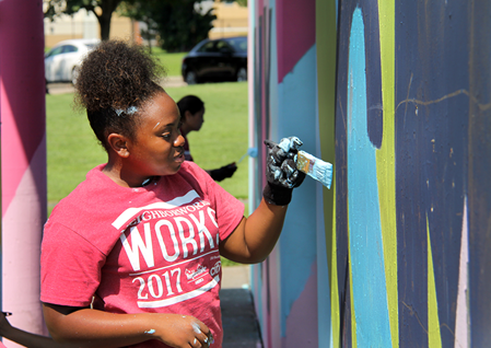 A volunteer helps paint a mural in Camden, New Jersey