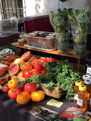 A table with various vegetables and fruits, including heirloom tomatoes, herbs, and grapefruit