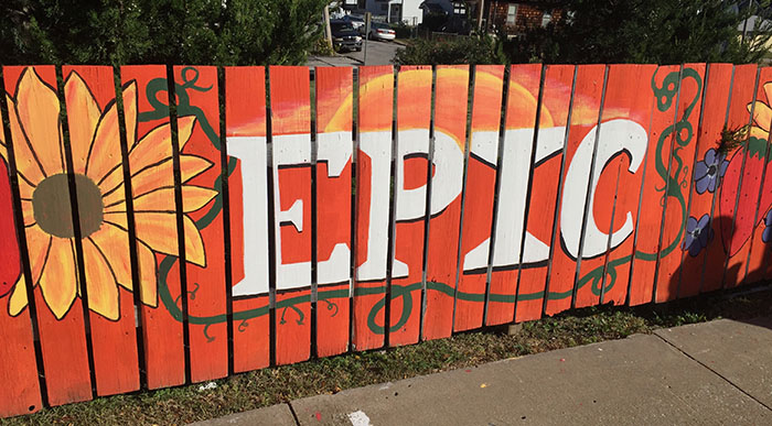 Orange mural on a fence with a sunflower and the word EPIC in white block letters