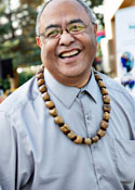 A Polynesian man wearing a blue button down and a wooden necklace smiles at the camera
