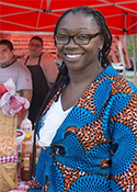 Angela Bannerman Ankoma stands beneath a red umbrella at the Sankofa Market