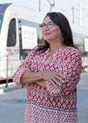 Diana Lerma Pfeifer wears a colorful shirt and stands next to a bus