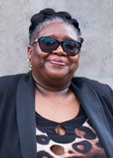 A black woman wearing sunglasses and a black blazer stands in front of a grey wall