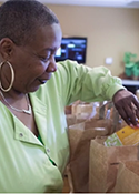 Mary Jones looks at bags of groceries being offered to the community