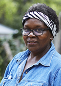 Sandra Robertson is a black woman wearing glasses and a denim shirt