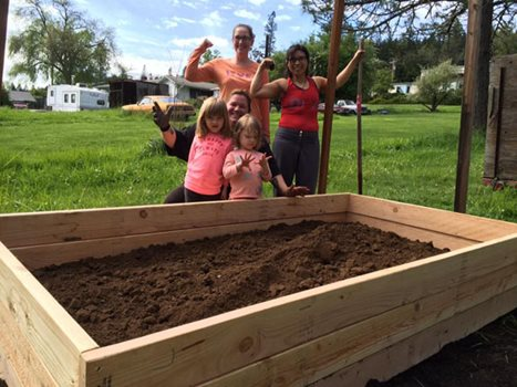 Two white girls and three white women stand in front of a plot of dirt