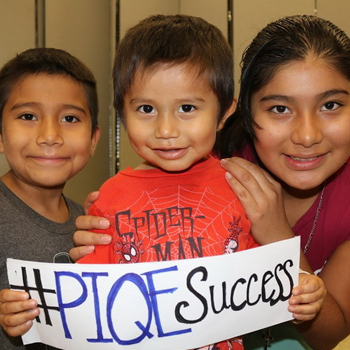 Three Latino children hold up a sign that says #PIQESuccess