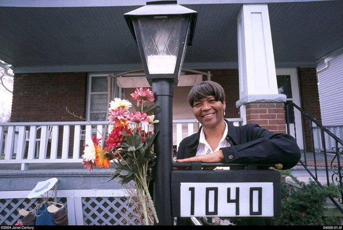 A black woman stands next to a street light in front of her home