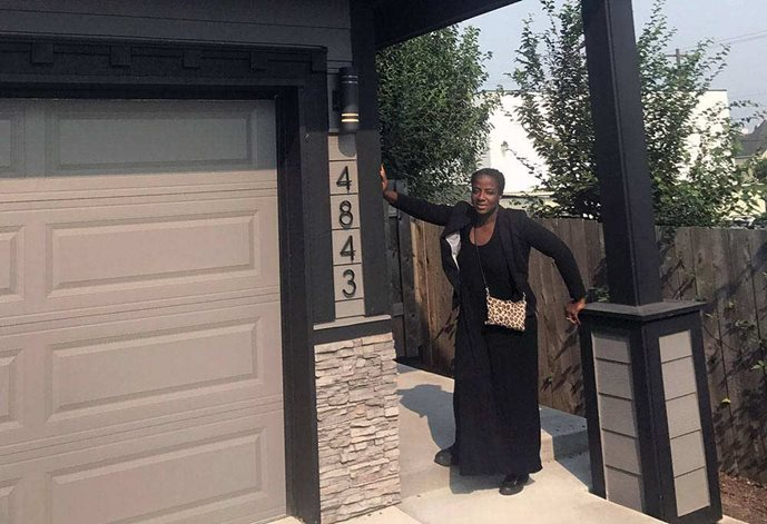 Charlene McGee, a black woman, stands in front of her new home