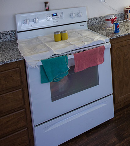 A stove with a pink and green dishcloth