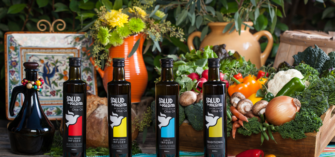A photo of four olive oil bottles on a colorful, festive table with potted flowers and fresh vegetables