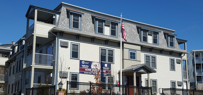 "An apartment complex that has a ""Home Sweet Home"" sign and the U.S. flag"