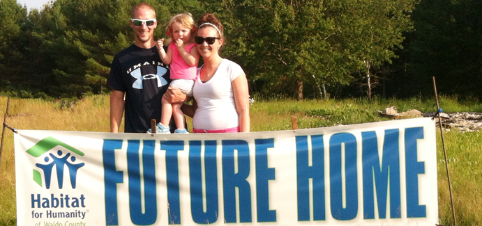 A white family stands in front of a Habitat for Humanity banner that says future home
