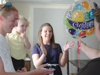 A white woman hands a Congrats balloon to a white woman with her white husband, who holds their daughter