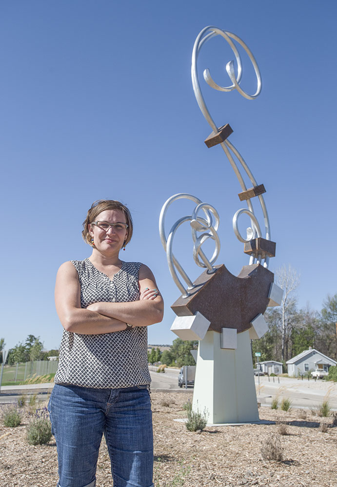 Erin Sorensen, a white woman, stands in front of a public art sculpture