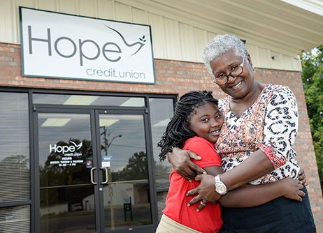 An older black woman and a child stand in front of Hope Credit Union