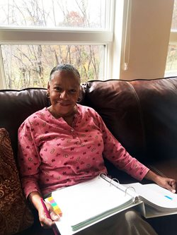 A black woman sits on a brown couch with a notebook in her lap