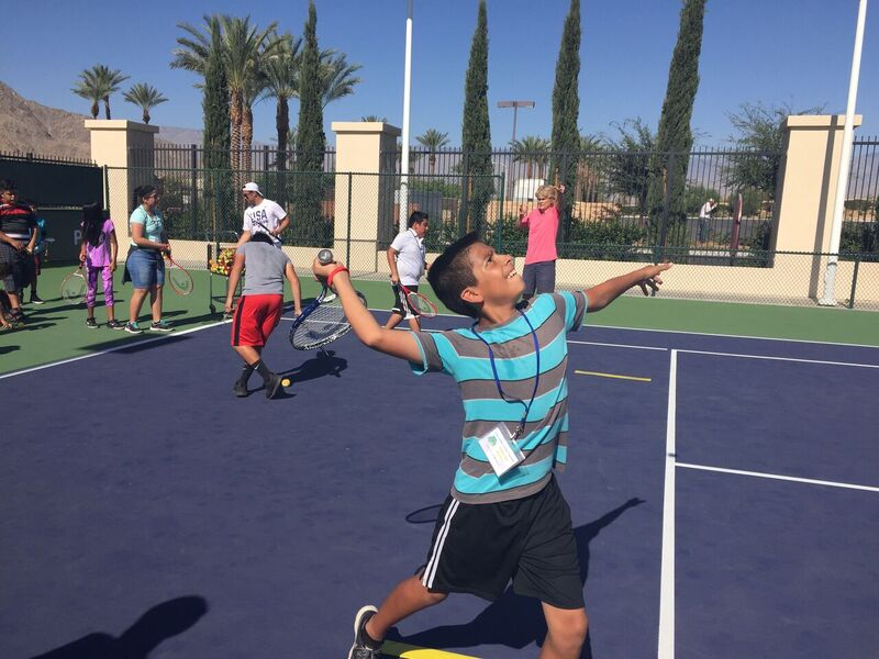 A boy wearing a striped blue and gray shirt looks up at the sky, prepared to volley a tennis ball back
