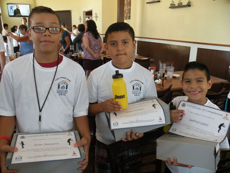 Three young boys wearing white sweatshirts hold certificates of completion