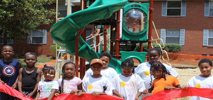 A group of black children stand in front of a green slide