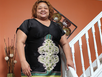 A black woman wearing a black dress stands in her newly-renovated home