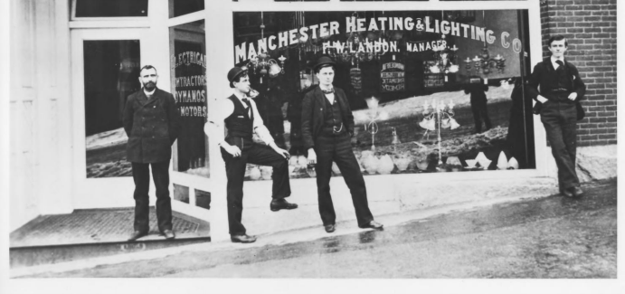 A historic picture of the Endicott Hotel. Four men are standing outside of a store window.