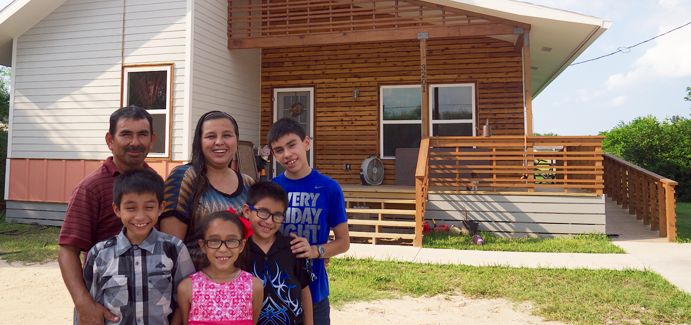 A family of six stand in front of their newly-renovated home