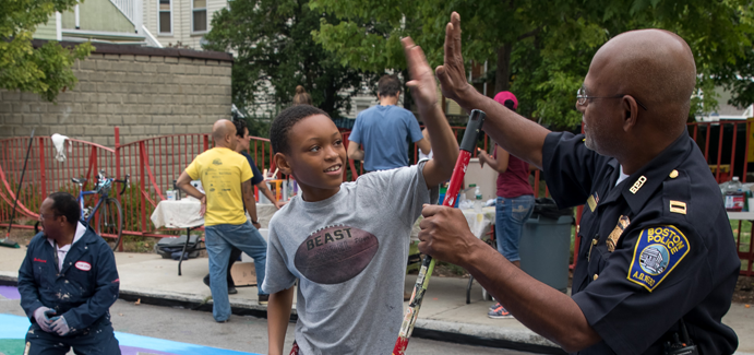 A black boy and a black police officer high five over a mural they've painted on a playground