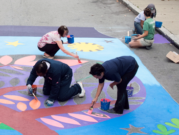 A mixed group of people paint a sidewalk