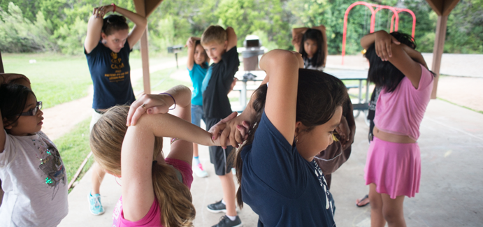 A group of kids stretch their arms during an exercise class