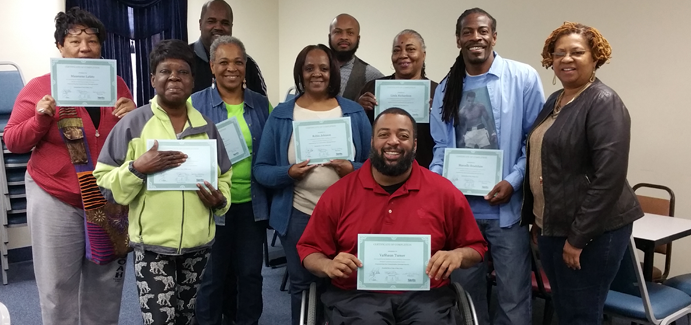 A group of black men and women hold up certificates