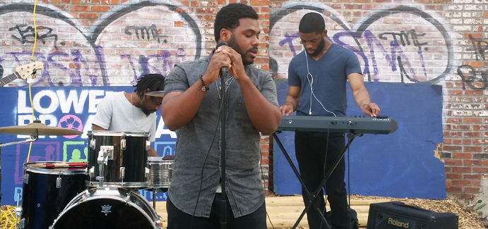 A black male singer tests the mic while two black men behind him test drums and a keyboard
