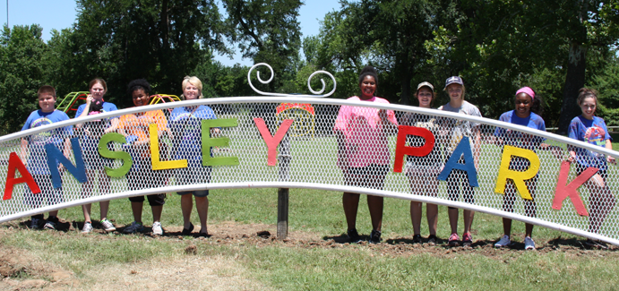 A group of kids stand behind a newly-painted Ansley Park sign