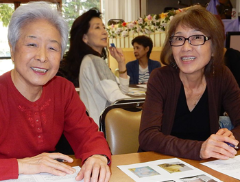 Two Asian seniors sit at a table learning about financial security