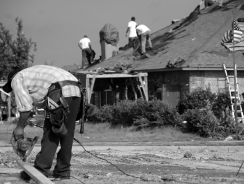 A group of people standing on top of a roof working on a house.