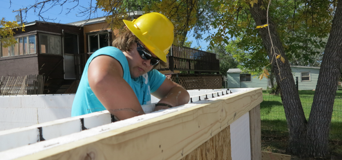 A student in a yellow hard hat putting together the foundation for a house.