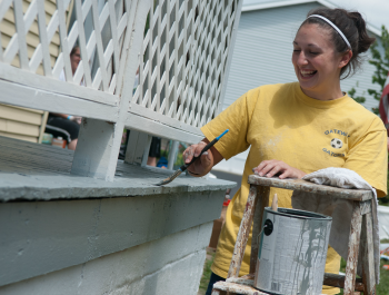 A young woman wearing a bright yellow shirt, paining a home's porch.