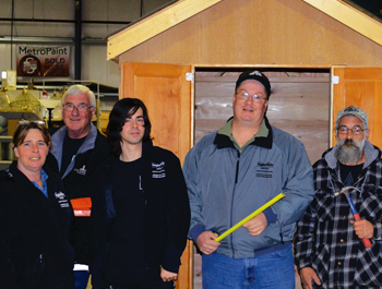 A mixed group of people stand in front of a shed