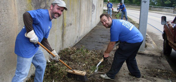 Two men wearing blue shirts and jeans help clean debris from the sidewalk