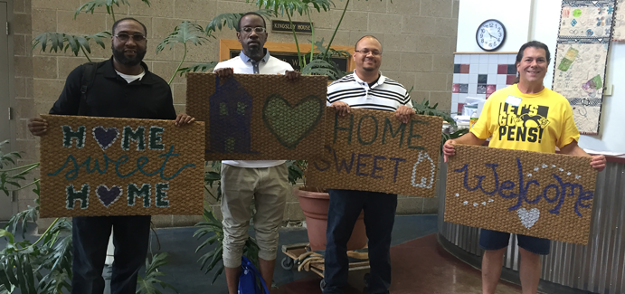 4 men hold home sweet home and welcome signs