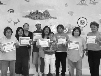A group of Native Americans hold up their homeownership certificates