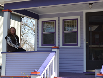 A white woman sits on the porch of her newly revitalized home