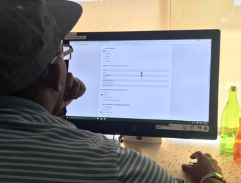 A black man wearing a black baseball cap and a striped shirt sits in front of a computer