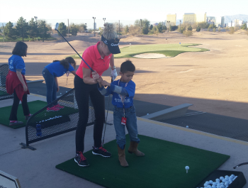 A young woman teaching a child to golf.