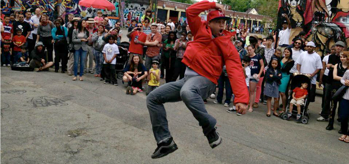 A dancer performing in the street as a large crowd looks on.