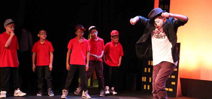 A group of young boys wearing red shirts and black pants watch another young boy wearing a half mask, black hat and black jacket leap into the air