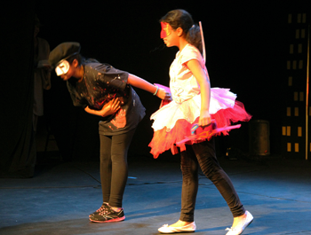 A young child wearing all black holds the hand of another child wearing a white and pink dress