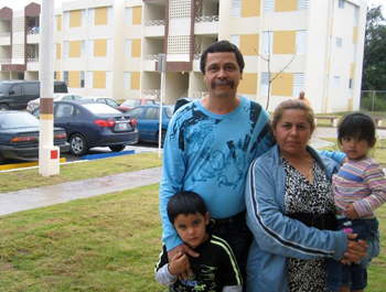 A family of four stand in front of a newly-constructed apartment building