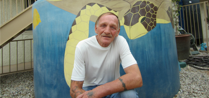 A man in a white long sleeve shirt sits in front of a mural looking straight at the camera.